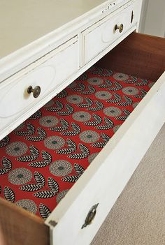 Drawer liners made with fabric, fabric-stiffening liquid, and doublesided tape.  Could also do this for lining backs of shelves.