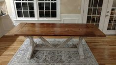 This is a trestle farmhouse table with a whitewashed base and reclaimed wood top