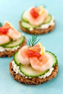 Love Canapes, cucumber, tartar sauce, shrimp, cocktail sauce, a small lemon wedge and some dill. I don't know what kind of bread it is on, Rye maybe?