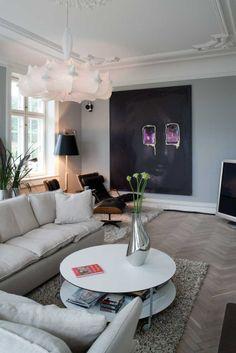 I den store pejsestue har familien valgt at male væggene mellemgrå, som fremhæver de mange detaljer i døre og vinduer. Selve den store sofagruppe består af sofaen Pillow fra DePadova. Det runde sofabord Giro er fra Zanotta. Vasen i stål er fra Georg Jensen. Den flotte lysekrone er tegnet af Philippe Starck for Flos. Den hedder Zeppelin.