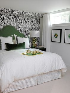 Bet you couldn't tell this sunny bedroom is actually located in a basement. Sarah maximized the small amount of natural light with plenty of crisp white in the room's walls, bedding and flooring. A bold, graphic wallpaper adds textural interest while the custom, arched headboard in a cheery green shade really pops.