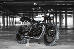 Based on a Yamaha TW 225, the Deus Ex Machina Two-Up Yamaha Motorcycle plusses the diminutive bike with a number of upgrades. The engine and wheels are done up with black paint, the better to contrast with the vintage Husky...