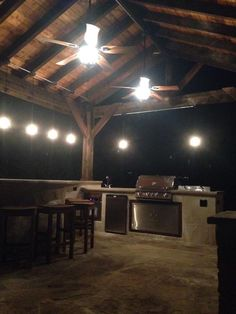 Beautiful outdoor kitchen complete with concrete countertops, pavilion style exposed rafter cover.