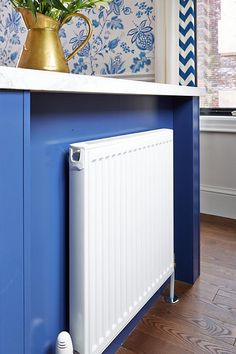 Since the basement was unfinished below the kitchen, we simply relocated the pipes to facilitate the installation of a new, slim profile rad that tucks under the far end of the island, Globe and Mail Real Potential Navy White Kitchen Radiator