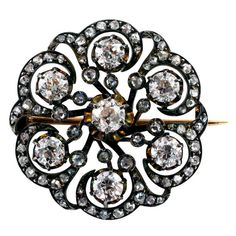 """Victorian French Diamond Brooch/Pendant. 4.50 Carats Victorian French Diamond Brooch  Circa 1870, This circular open design features seven very bright old mine-cut diamonds on a ground of scrolling motifs set throughout with rose-cut diamonds, together totaling approximately 4.50 carats, mounted in 18 karat gold and silver, French hallmarks, the back side fitted with a pair of loops suitable for hooking onto a chain, approximately 1 1/4"""" diameter."""
