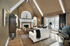 Huge living room with 2-story cathedral ceiling with exposed white beams and matching white mantle fireplace