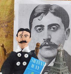 Doll Miniature Marcel Proust French Author  This handmade art piece is a must have for the fan of Marcel Proust! My hand designed, unique art doll character is wearing a two piece black suit accented with wide black collar and white buttons. Marcel has a hand painted face, and holds a tiny replica of one of his works while sitting and pondering at his writing desk. Extra detailing is the tiny hurricane lamp on his desk, a quill and paper, a book of another of his works, and for fun, a…