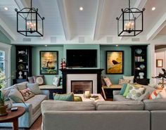 Seafoam walls, sectional couch, book shelves, and lots of pillows.