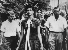 A crowd of youths taunt Dorothy Counts, 15, as she walks to the previously all-white Harding High School to enroll, September 4, 1957, Charlotte, NC. Leaving the school, she was pelted with trash, small sticks and pebble