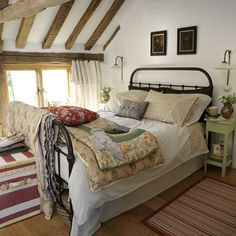 Comfy country bedroom with iron bed frame and mixed linens in lots of time-worn patterns.  Exposed wood ceiling beams