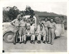 1942- U.S. war correspondents pose for photo at Port Moresby, New Guinea. Front left to right: Ed Widdis, AP photographer; Harold Guard, United Press: Al Noderer, Chicago Tribune; Pat Robinson, INS; Byron Darnton, New York Times; Dean Schedler, AP; and Jack Turcott, New York Daily News. Rear left to right: Martin Barnett, Paramount Newsreel and Frank Prist, ACME.