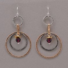 Surrounding Circles Earrings.  Circles abound in gold fill, oxidized sterling, and polished silver.  Each hand hammered and part of a supporting cast to a beautfiul faceted garnet.  These handcrafted earrings are complimented with a brushed gold fill accent bead.
