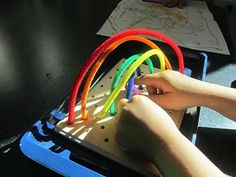 need R to drill holes in a piece of wood and hand E some pipe cleaner to make her own rainbows