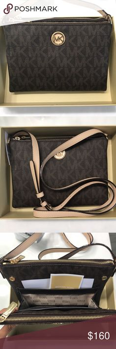 Michael Kors Crossbody Bag This bag is new and still has a tag and comes with the box. It has two zipper pockets and buttons that reveal inside pockets as shown in the pictures. The strap is also adjustable as shown. Michael Kors Bags Crossbody Bags