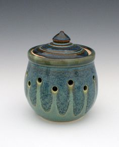 This lidded garlic keeper is a wonderful gift for yourself or a favorite cook in your life. The hand drilled holes will help let your garlic breathe. Fresh garlic is best stored in a cool and dark place which will help maximize the shelf life of your garlic. Its glazed in a beautiful jade green glaze with a blue overlapping glaze. Definitely a decorative way to store your garlic in your kitchen.    4 Widest Point (3 3/4 at rim) X 5 Tall IN STOCK AND READY TO SHIP    All of my work is wheel…