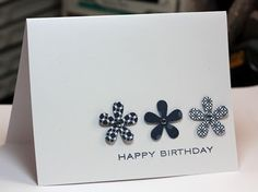 """handmade birthday card ... Clean & Simple by lorie ... line ofthree five petal flowers cut out of three different navy blue patterned papers .... """"happy birthday"""" stamped below ... lots of white spece ... luv it!"""