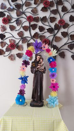 Arco com flores de papel crepom, decorando a imagem de Santo Antônio.