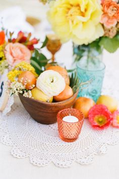 flowers in mason jars, bowl with oranges and lemons and flowers, on sewn together doilies