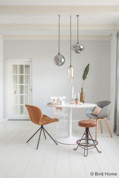 Een doorkijk naar de ronde tafel en een mix van stoelen   Binti Home blog : Interieurinspiratie, woonideeën en stylingtips