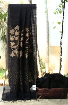 CLASSIC BLACK MATKA SILK HAS GLAMOROUS KORA PALLU WITH DELICATE GOLD JAMDANI FLORAL WEAVE AND GOLD SEQUIN WORK WHICH GIVES THE SAREE A DREAMY LOOK. THE RED CONTRAST BLOUSE GIVES THE SAREE MODERN TW...
