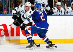 San Jose Sharks forward Tye McGinn sends a pass through Nick Leddy of the New York Islanders (Oct. 16, 2014).