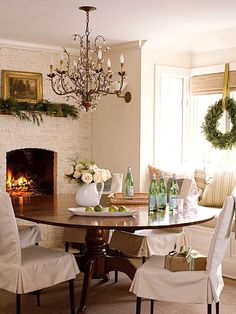 Relaxed Dining Room - The exposed brick wall and fireplace in this Sag Harbor, New York, dining room was once red brick. Painted the same shade of white as the walls and then dressed, the bricks patina looks vintage and cottage chic. Dining Room Design, Dining Area, Kitchen Dining, Round Dining, Round Tables, Kitchen Nook, Dining Chair Slipcovers, Dining Chairs, Dining Rooms