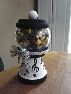 The candy jar I made for my children's piano teacher. It's not quite the same as others I've seen out there. I used: 1 terra cotta pot, 2 terra cotta bases, 1 glass bowl, 1 wooden knob, a set of note stickers, acrylic paint, hot glue and a lil' ribbon. Took me less than an hour and only cost about $7!