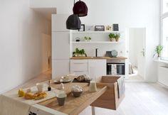 Cucina a pianta aperta con mobili bianchi su misura e un iconico tavolo con spazio per lo storage Clark Desk di llot llov. A pensare l'interior di questo bilocale berlinese è l'interior designer Sarah Van Peteghem