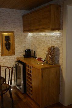 """O """"Cantinho do vinho"""" ocupa uma parte da sala de estar neste apartamento em São Paulo (SP). O espaço foi feito em madeira freijó e inclui uma adega climatizada embutida. Já a parede de tijolos de demolição contribuem para um ar mais rústico. """"O único critério utilizado foi o cuidado de manter as garrafas na posição horizontal para não secar a rolha"""", explica a arquiteta Jaqueline Salvador, do escritório Fratelli Interiores."""