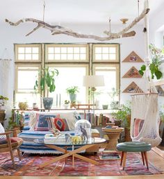 A global bohemian living room design featuring a unique driftwood lighting fixture and a hanging hammock chair - Global Decor & Decorating Ideas - stylebyemilyhenderson.com
