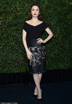 Pretty as a picture: Lily Collins wore a black ribbed top with large collar, teamed with a shiny embroidered skirt as she stepped out at the Charles Finch pre-Oscars party on Saturday night