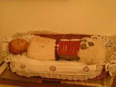 Madonna Bambina, Alcamo, Monastero Angelo Custode. La Madonna bambina é in cera e avvolta in fasce tempestata di corallo e con trinetta in argento. Il manufatto presenta solo il volto ed il collo in cera, ha gli occhi in vetro e la caratteristica delle labbra socchiuse attraverso le quali si notano due denti. Elegante è il giro di roselline rosa in seta che chiudono la fasciatura in raso, arricchita da merletto bianco. L'opera è decorata con una fascia di tartaruga, una di fili di grani di…