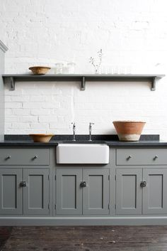 great kitchen styling idea - grey cabinets, farmhouse sink, black countertops, exposed open shelving
