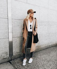 tan trench coat + baseball cap + white tee + black sunglasses + dark jeans + white shoes