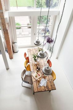 Industrial eat in kitchen design rustic dining table colorful modern dining chairs brightly white interior space Pallet House, Rustic Kitchen Design, Industrial Interior Design, Modern Dining Chairs, Dining Table, Dining Area, Dining Room, Wood Home Decor, Reclaimed Wood Furniture