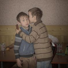 Åsa Sjöström - 2015 Igor whispers into his friend Renat's ear, at a school in northern Moldova. It is Igor's birthday, and his grandmother has given him chocolate to hand out to his classmates. Moldova is Europe's poorest country. In the past 10 years, one-third of the working population has gone abroad in search of better-paying jobs. Children often find themselves looked after by elderly relatives, or left in orphanage boarding schools. Igor has a twin brother.