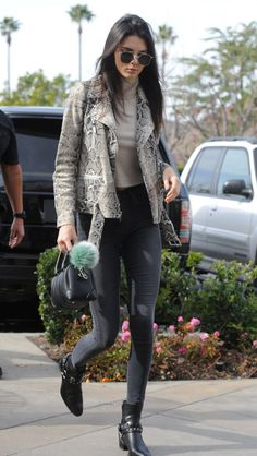 Kendall Jenner wears an Elizabeth and James python jacket, dark jeans, a beige turtleneck, and Saint Laurent boots witha Givenchy duffel and Fendi fur pompom key chain