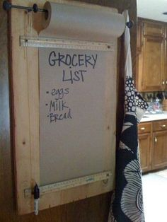 Mount a small curtain rod inside a cabinet or pantry. Below tack a ruler to hold the paper down. Get a roll of craft paper and ta da, you have an instant and accessible place to jot down lists, recipes, numbers, etc. Want this for the back door!!