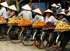 Vietnam, Hanoi, fruit vendors on bikes