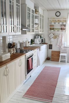 White kitchen, wood countertops. Lighter than in this picture though. Windowed cabinets, rug for warmth.