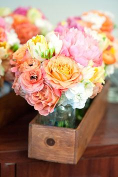 Arrangements of pastel roses, camellias & tulips. Love the blue mason jars in rustic boxes!
