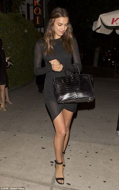 Simple yet chic: The 28-year-old's black bodycon dress featured a quirky wrap hem and semi-sheer sleeves