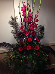 Henley in Arden golf club masquerade ball for the air ambulance pedestal stand in glass vases with gladi gerbera roses carnations and black feathers