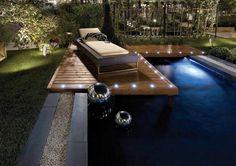 luminaire extérieur LED : plage de piscine en bois composite avec des spots à LED et bain de soleil en résine tressée