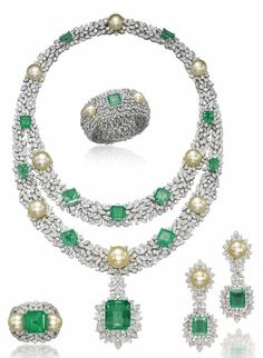 A GROUP OF CULTURED PEARL, EMERALD AND DIAMOND JEWELLERY   Comprising a necklace composed of diamond-set oval-shaped elements, forming two rows at the front, enhanced by cream cultured pearls and rectangular-cut emeralds, to the detachable similar pendant, a bangle, a pair of ear pendants and a ring en suite, mounted in gold