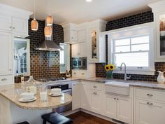Crisp white cabinets brighten dark brown subway tile walls in this transitional kitchen. A white farmhouse sink blends with the white cabinets and neutral countertops, while a kitchen peninsula provides a spot for quick meals without sacrificing space.