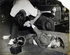 Many of Weegee's photographs, like this shot of a corpse being examined while lying on a New York City sidewalk in 1941, are not for the faint of heart.