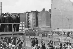 President John F. Kennedy stands on an observation platform as he looks into East Berlin over the wall on June 26, 1963.
