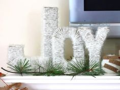 """A Rustic Winter Wonderland Christmas Mantel:    Making a statement with a touch of warm texture, Kraft letters spelling """"Joy"""" are covered in icicle white yarn."""