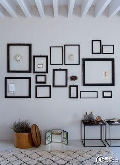 Collection de vieux cadres en bois noir dont certains décorés d'objets, tapis berbère chez 'Bersanetti Tappeti', boutique de décoration à Pa...